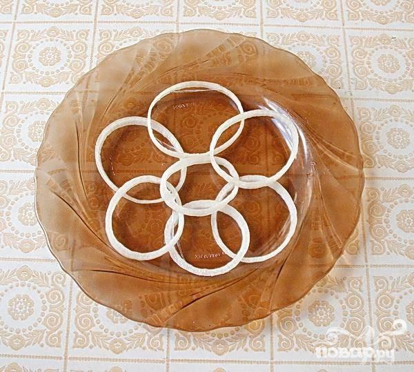 2.Отделяем друг от друга кольца лука, и внахлест, несколько колец укладываем на тарелку. Это будет основа салата.