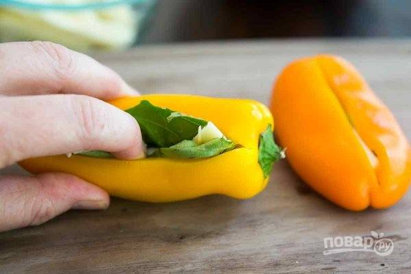 1. Перец вымойте и обсушите. Сделайте небольшой надрез и аккуратно достаньте семена. Еще раз промойте при необходимости. В серединку вложите кусочек сыра и листик базилика.