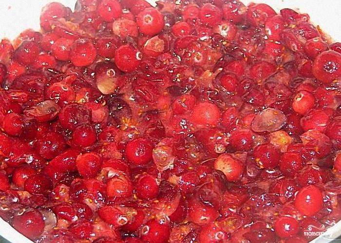 2. Ягоды клюквы моем, перекидываем на дуршлаг, чтобы ушла лишняя вода. Перекладываем их в миску и разминаем ложкой или давилкой для картофеля в кашицу, после того, как ягоды выпустили сок, перекладываем их в воду с сахаром.