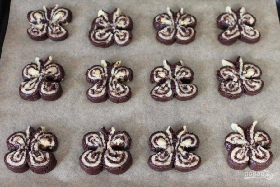 Каждое печенье прижимаем с двух сторон, чтобы получилась бабочка и кладем на противень, покрытый пекарской бумагой.
