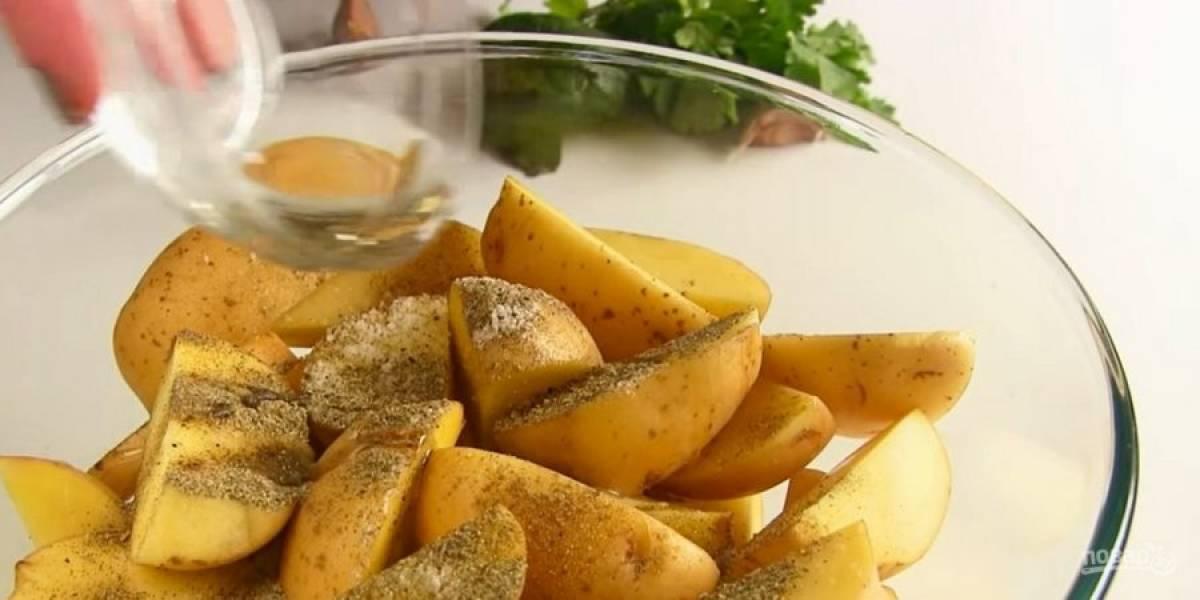2.  Переложите картофель в миску, посолите и добавьте специи (паприку, кориандр, черный и красный молотый перец, базилик, орегано и проч.) Добавьте растительное масло, хорошо перемешайте.