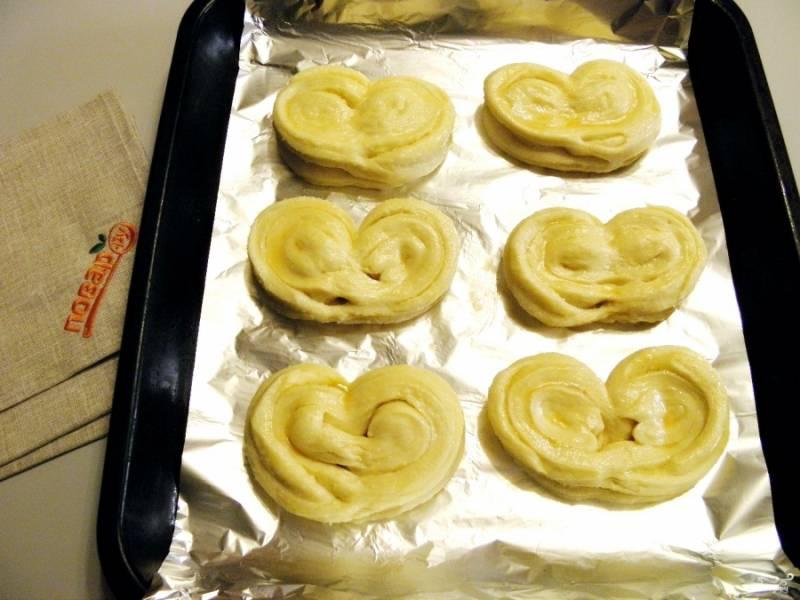 Перенесите плюшки на противень, я застелила его фольгой и смазала кулинарным жиром. Дайте плюшкам минут 30 расстойки. Обязательно прикройте чистой салфеткой или пленкой (чтобы плюшки не прилипли к ней, смазывайте маслом растительным). Спустя 30 минут смажьте плюшки яйцом и посыпьте сахаром. Отправьте в духовку при 190 градусах на 30-35 минут.