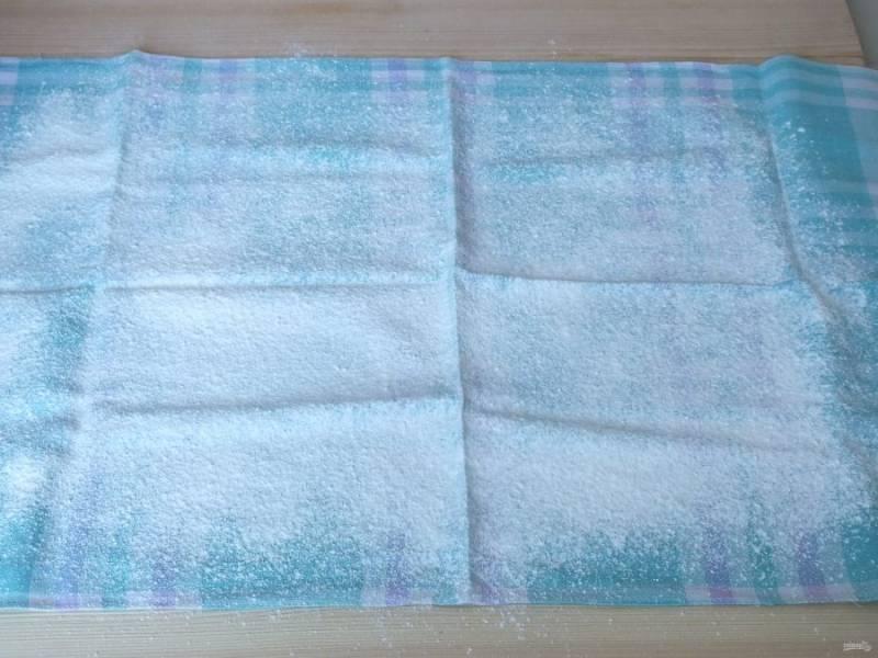 Пока готовится корж подготовьте полотенце на рабочей поверхности, обильно присыпьте его сахарной пудрой.
