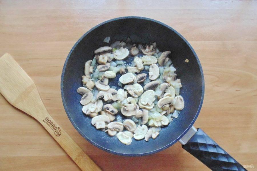 Добавьте подсолнечное масло и тушите лук с грибами 7-8 минут, перемешивая.