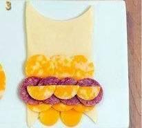 Уложите ряд тонко нарезанной колбаски и полукружки сыра.