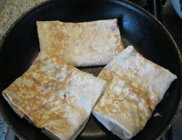 7. Сухую сковороду разогреть и выложить конвертики швом вниз. На среднем огне обжарить до золотистой корочки с двух сторон. Вот и все, аппетитный и простой лаваш с сыром, яйцом и зеленью в домашних условиях готов.
