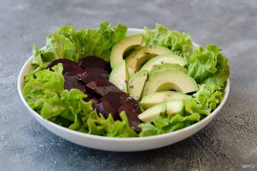 Выложите на листья салата свеклу и авокадо. Полейте заправкой.