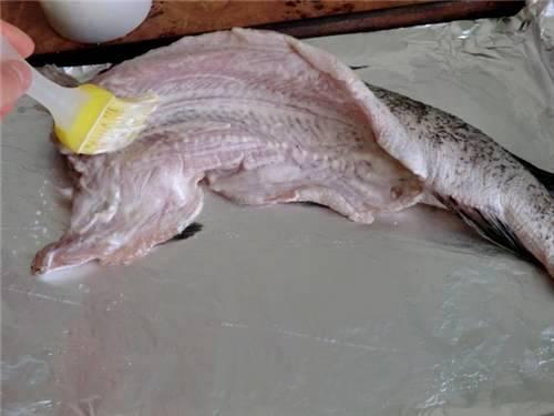 На противень выкладываем лист фольги, а на него кладем рыбу, натираем ее солью и смазываем сметанным соусом со всех сторон.