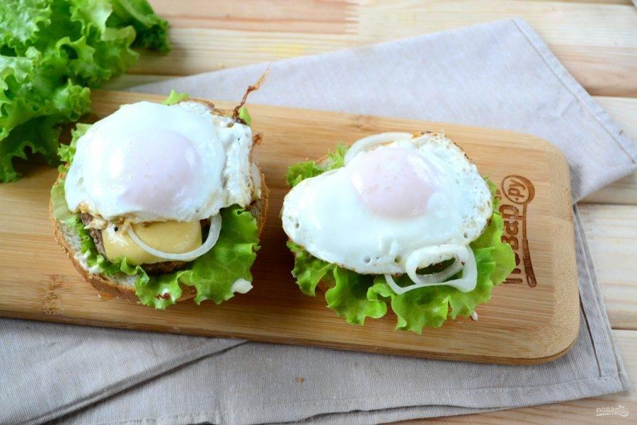 На котлету положите 3-4 колечка лука. Приготовьте 2 яичницы: яйца разбейте на сковороду с небольшим количеством растительного масла, посолите, накройте крышкой и готовьте на среднем огне, пока белок на желтке из прозрачного не станет белым. Очень удобно готовить яичницу со стеклянной крышкой, чтобы наблюдать за процессом. Готовую яичницу положите сверху на лук.