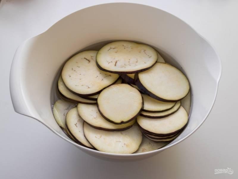 Нарежьте баклажаны кольцами и замочите в холодной воде с солью на 30-40 минут. Это необходимо, чтобы из овоща вышла вся горечь.