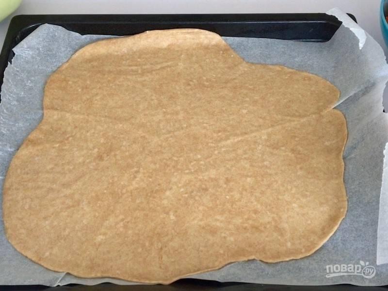 Отдохнувшее тесто раскатайте между двумя листами бумаги для выпечки и уложите на противень.