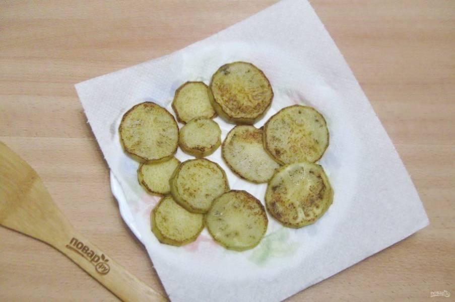 Обжарьте кружки баклажана с обеих сторон и выложите на тарелку с бумажным полотенцем для удаления лишнего масла.