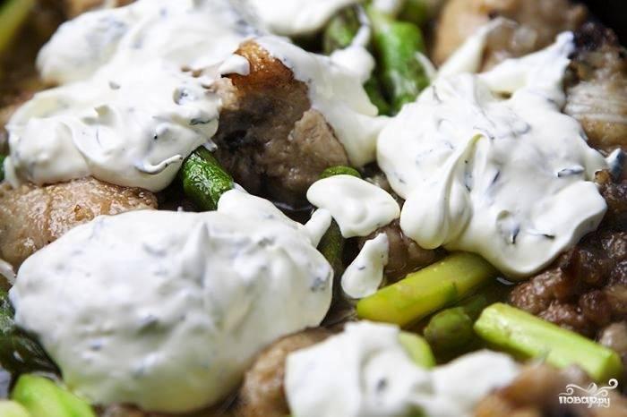 За 3-4 минуты до готовности курицы добавляем в сковороду сметану и измельченный тархун. Перемешиваем, накрываем крышкой и тушим на среднем огне еще 3-4 минуты.