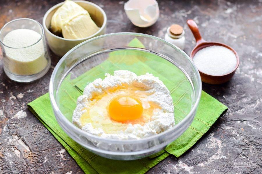 Выберите глубокую удобную емкость, переложите в нее порцию творога. Если творог крупнозернистый, протрите его через сито. К творогу добавьте куриное яйцо.