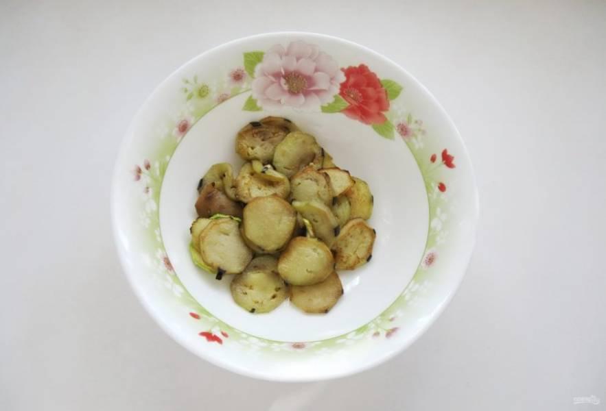 Жареные кружки баклажана и кабачка выложите на бумажное полотенце, чтобы оно впитало лишний жир. Кружки баклажана отправьте в салатник.