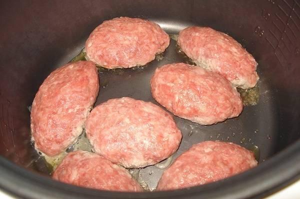 """Для начала приготовим фарш, для этого смешиваем свиной и говяжий фарш, добавляем размоченный в молоке хлеб, яйцо, измельченный лук, солим и приправляем специями, замешиваем фарш. В чашу мультиварки выкладываем сливочное масло, устанавливаем режим """"Выпечка"""" и время 40 минут. Выкладываем в мультиварку котлеты."""