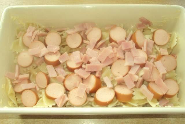 Сосиски очищаем от шкурок и нарезаем кружочками. Выкладываем сосиски к макаронам. Можно выложить по верху, а можно перемешать с макаронами.