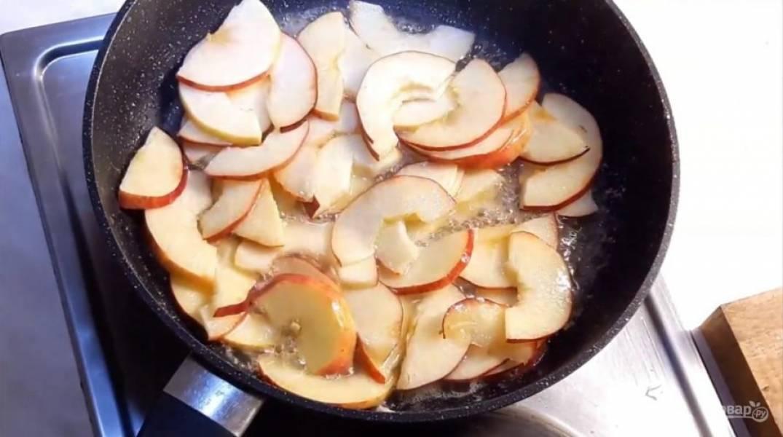 3. Яблоки разрежьте наполовину и удалите из них середину. Нарежьте их тонкими полосками и отправьте на сковородку, в которой разогрейте сливочное масло с сахаром. Немного подержите яблоки (до полупрозрачности) в кипящем масле.