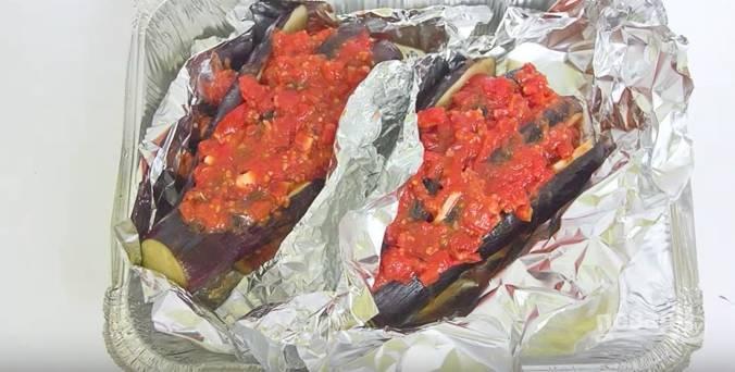 Выложите начиненный баклажаны на фольгу в форму для запекания. Сверху на каждый — томатный соус. Заверните в фольгу. Запекайте в разогретой до 180 градусов духовке 40-50 минут. После достаньте, посыпьте тертым сыром и поставьте ещё минут на 7-10 подзапечься.