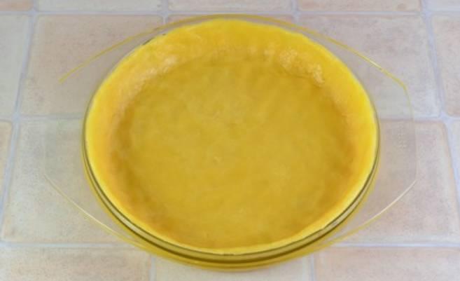 Выкладываем тесто в форму (20-25 см.). Равномерно его распределяем, формируем бортики (1-2 см. по высоте). Ставим форму на 20 минут в холодильник.
