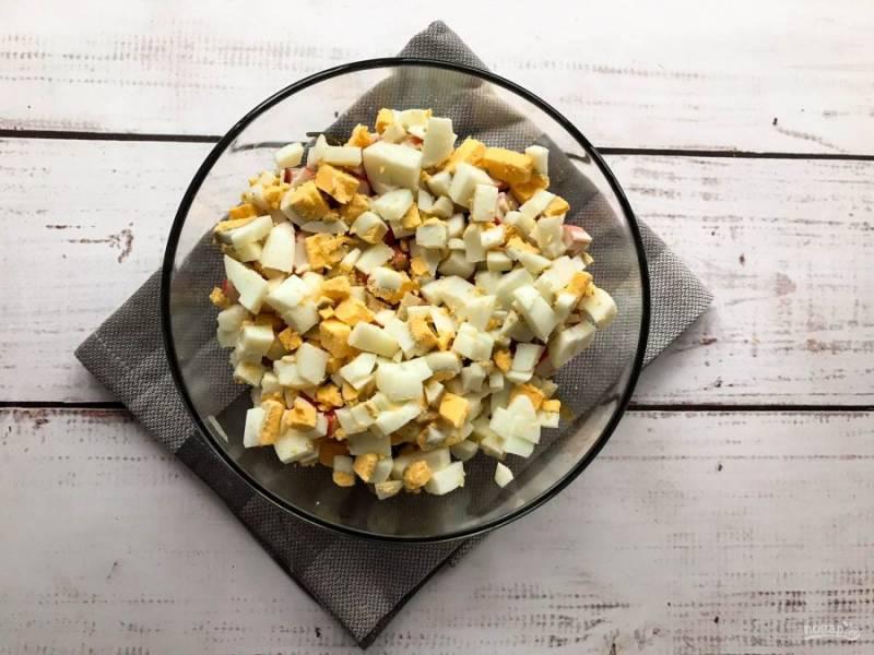 Яйца очистите от скорлупы, нарежьте небольшими кусочками и высыпьте в тарелку.