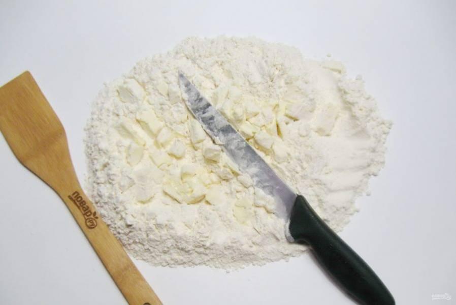 С помощью ножа порубите сливочное масло с мукой до состояния крошки.