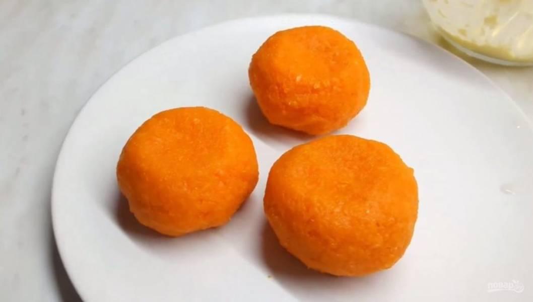 3. Затем влажными руками сформируйте небольшую лепешку из моркови и заверните в нее шарик. Морковь должна хорошо прилипать к закуске. Немного прижмите шарик, чтобы он стал похожим на мандарин.