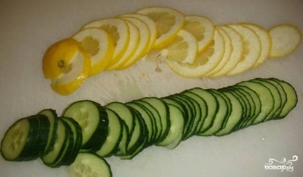 2. Огурчик и лимон вымойте как следует, обсушите немного и нарежьте тонкими колечками. Иногда кроме лимона добавляют также апельсин, рекомендую вам попробовать оба варианта.