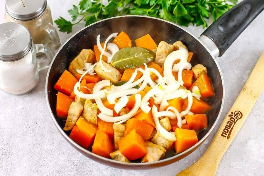 Очистите репчатый лук, нарежьте полукольцами и добавьте в емкость. Перемешайте и обжарьте еще 3 минуты, затем накройте емкость крышкой и пропарьте все на минимальном нагреве примерно 5 минут до готовности мяса и тыквы.