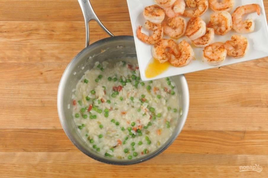 5. Затем в ризотто добавьте горошек и помидоры. Варите ингредиенты 2 минуты. Потом натрите сыр и добавьте масло. Через 3 минуты добавьте креветки, перец и соль.