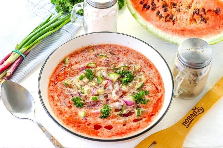 Промойте и очистите красный лук, промойте огурец, срежьте хвостики. Нарежьте половинки овощей мелкими кубиками. Промойте перья зеленого лука и измельчите и его. Добавьте все нарезки в арбузно-томатную массу. По желанию можно использовать и сладкий болгарский перец разного цвета.