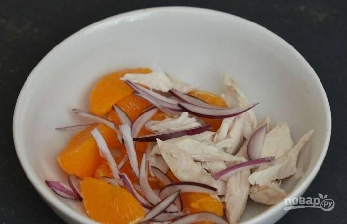Соедините в небольшой пиале или салатнице очищенные дольки мандаринов и отварное куриное мясо. Затем очистите от шелухи лук и вымойте его. Нарежьте лук тонкими дольками и добавьте его к остальным ингредиентам.