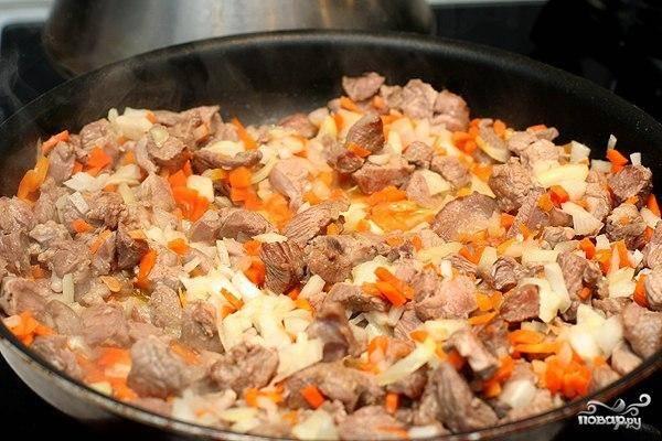 Затем в ту же сковороду кладем мелко нарезанные лук и морковь. Обжариваем, помешивая, 2-3 минуты.