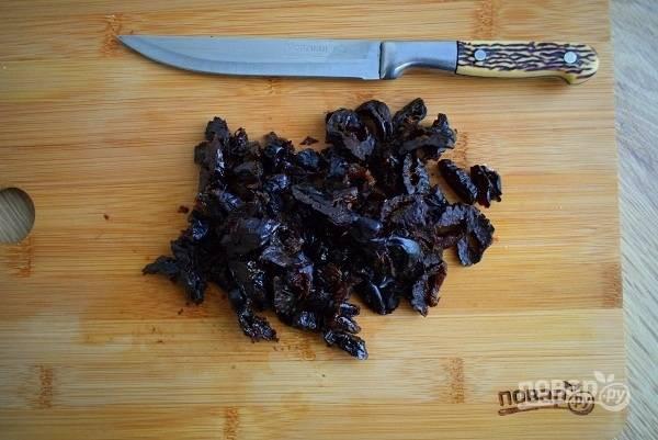 Чернослив мелко нарежьте с помощью ножа.