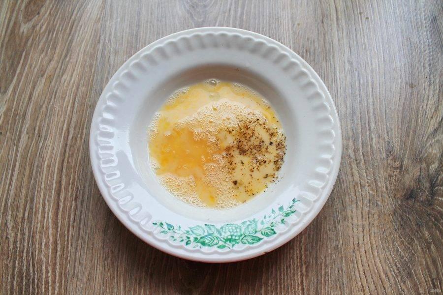 В чашку разбейте яйцо, посолите и перемешайте вилкой. Взбивать его не нужно, достаточно сделать его однородным, поперчите и перемешайте снова.