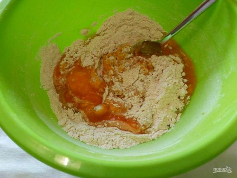 Влейте остывшую тыквенную массу и подсолнечное масло в сухую смесь, тщательно перемешивая компоненты ложкой.