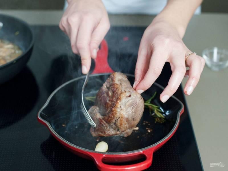 Разогрейте на сковороде масло. Добавьте в него розмарин и зубчик чеснока. Обжарьте мясо со всех сторон до золотистой корочки.