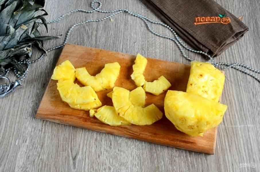 Примерно половину мякоти ананаса нарезаем на крупные ломтики так, как на фото. Количество ломтиков должно быть равно количеству кусочков курицы.