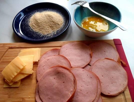 1. Если вы не знаете, что приготовить на завтрак - побалуйте своих близких разнообразными закусками. Например, колбасой в кляре с сыром в домашних условиях. Нарежьте колбасу колечками толщиной 3 мм. Приготовьте миску с сухарями. В другой глубокой мисочке взбейте вилочкой яйцо. Тонкими пластинками нарежьте сыр.