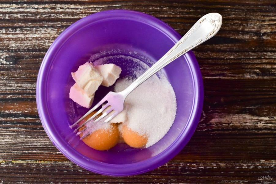 Отделите белки от желтков. В миску выложите желтки, к ним добавьте сахар и сливочное масло комнатной температуры.