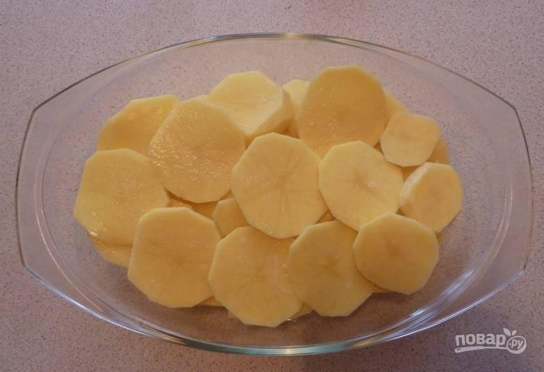 Картофель промываем и очищаем. Нарезаем тонкими дольками и складываем в форму для запекания, смазанную маслом. Солим и перчим по вкусу.