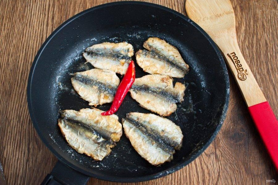 На сковороде разогрейте масло. Чеснок разрежьте пополам, обжарьте с одной стороны, снимите со сковороды. На сковороду выложите рыбу, острый перец и розмарин. Обжарьте рыбку с двух сторон до румяной корочки, снимите со сковороды.