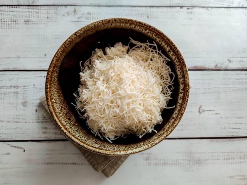 Сыр натрите на мелкой терке и добавьте к творогу.