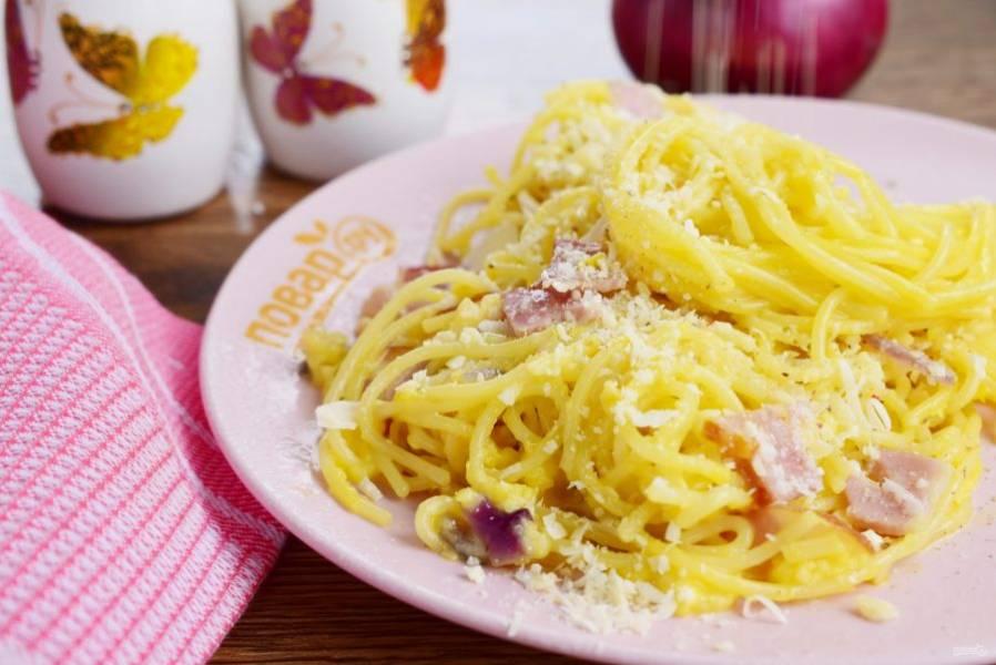В горячие спагетти добавьте обжаренные лук, кусочки бекона, влейте соус, перемешайте. Сверху посыпьте тертым пармезаном и черным перцем. Приятного аппетита!