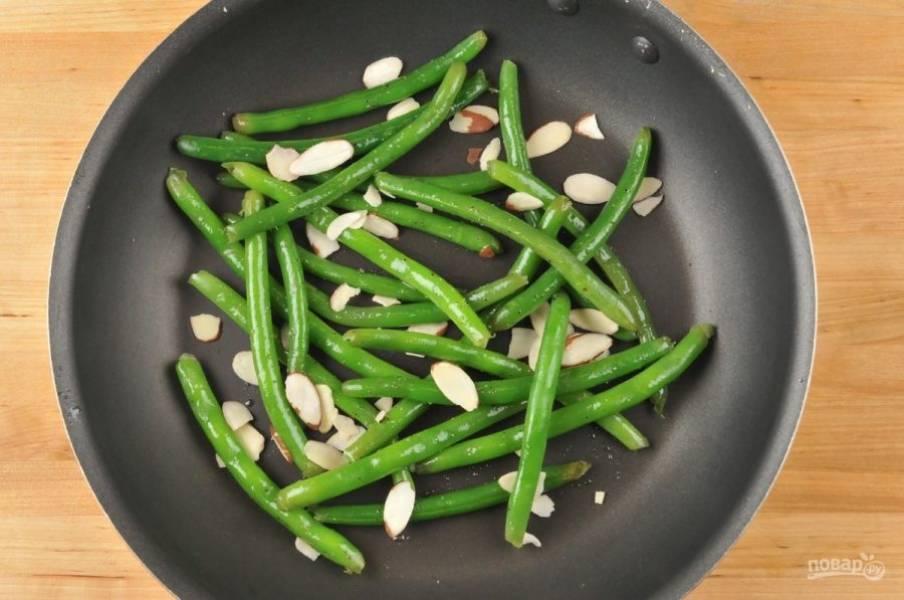 5. Затем в сковороду выложите фасоль. Добавьте воду и соль. Доведите воду до кипения и готовьте фасоль 2,5 минуты. После этого добавьте 1 ч. ложку масла и миндаль. Перемешайте ингредиенты, через 1 минуту выключите огонь.