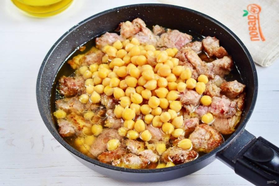 4.     Добавьте нут. Влейте горячую воду. Тушите на среднем огне в течение 20 минут, до выпаривания жидкости. Полейте мясо лимонным соком, готовьте еще пару минут.
