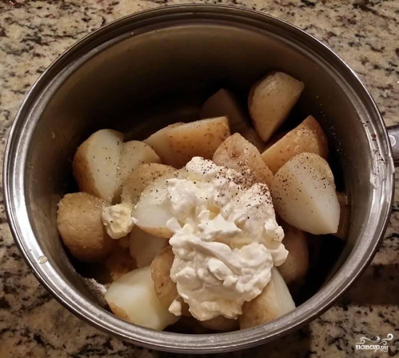 6. С картофеля слейте воду, добавьте немного сливочного масла, сметану. Посолите и поперчите по вкусу. Разомните в пюре и вбейте яйцо. Еще раз как следует перемешайте.