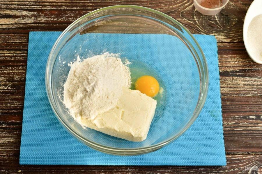 В миску вбейте куриное яйцо, выложите творог, всыпьте соль, муку.