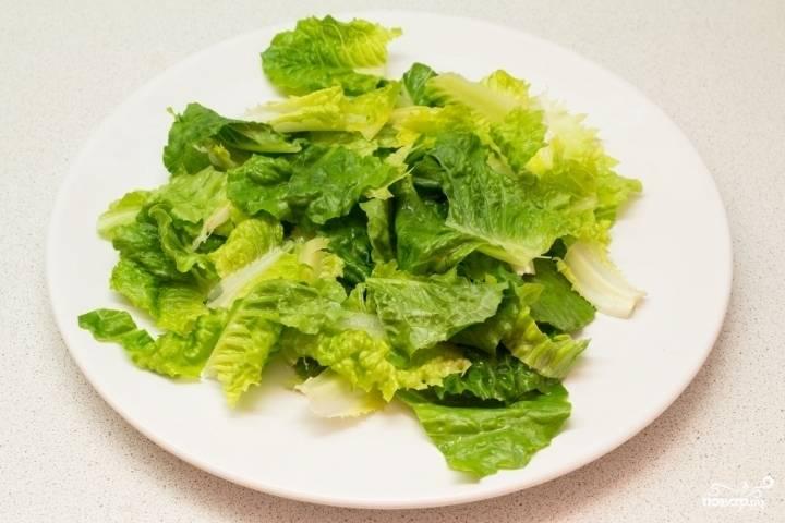 Салатные листья промойте, обсушите и порвите крупно руками. Выложите их аккуратно на тарелку. Кстати, можно использовать микс салатом, так будет интереснее и вкуснее, если вы любитель зелени.