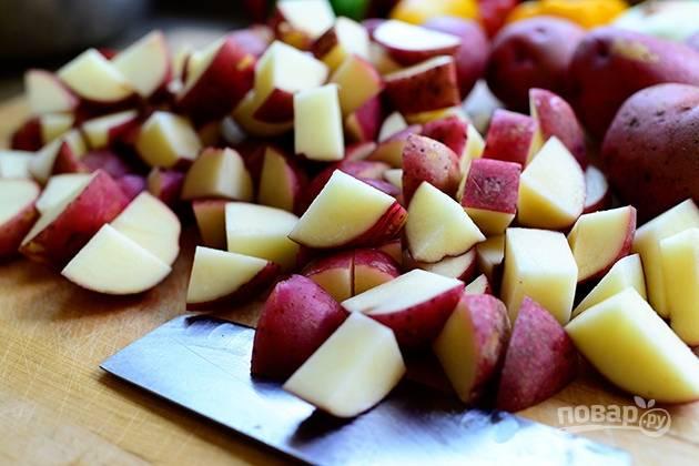 1. Разогрейте духовку до 240 градусов. Нарежьте картофель на четыре части.